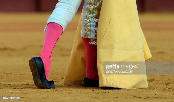 Spanish bullfighter Alfonso Cadaval walks holding his 'capote' during a bullfight at the Real Maestranza bullring in Sevilla on September 30 2018 The...