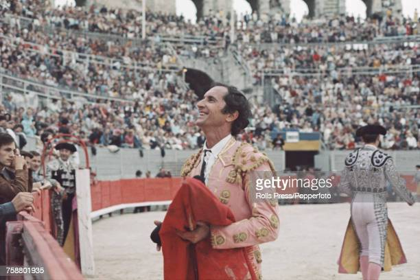 Spanish bullfighter Luis Miguel Dominguin pictured holding a red cape in the Arles Amphitheatre bullring during a bullfighting event in Arles France...