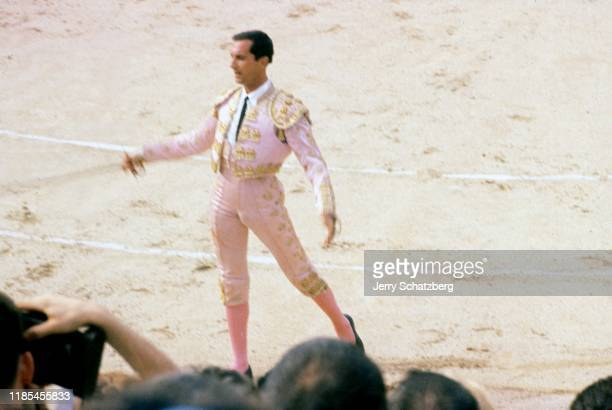 Spanish bullfighter Luis Miguel Dominguin presents his espada in front of a crowd in Arles Amphitheater Arles France 1959