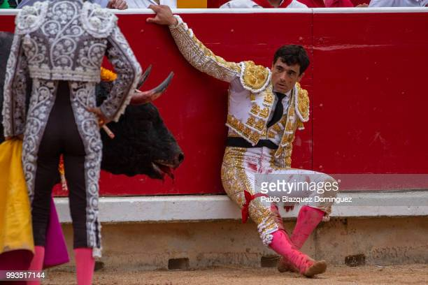 Spanish bullfighter Paco Urena sits next to a dying bull from Puerto de San Lorenzo's fighting bulls after Urena was gored on his leg when trying to...