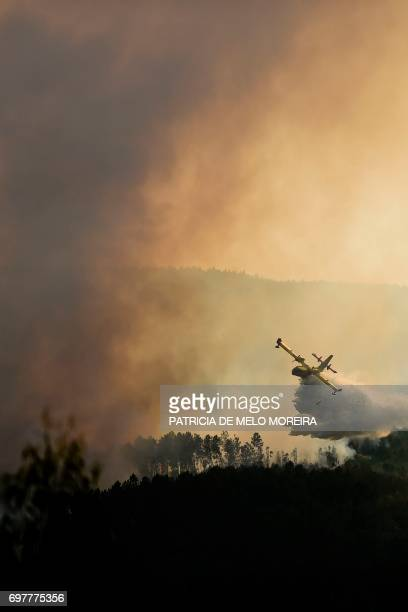 Spanish Canadair firefighter plane drops its load over a wildfire in Castanheira de Pera on June 19, 2017. More than 1,000 firefighters are still...