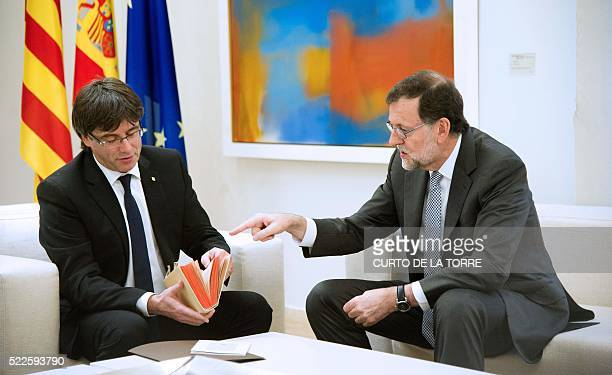 Spanish caretaker Prime Minister Mariano Rajoy points at a copy of 'Don Quixote' which he presented to Catalan Prime Minister Carles Puigdemont...