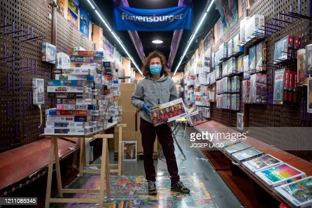 Spanish Caroline Belles head of Puzzle Mania, poses in her shop in Barcelona, Spain, on April 22, 2020 during the COVID-19 coronavirus pandemic. -...