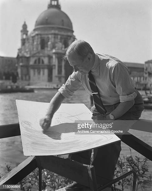 Spanish catalan painter Joan Miro wearing a striped ciphered shirt a striped tie and a watch sitting on a fence in front of la Salute church drawing...
