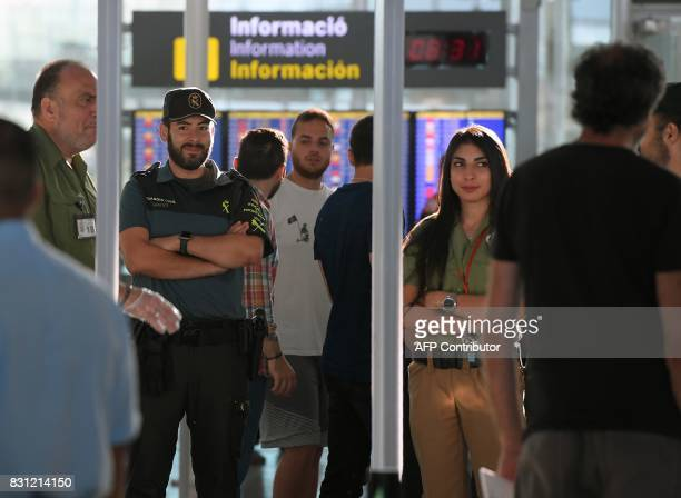 A Spanish civil guard checks passengers as they pass through a metal detector on August 14 2017 at Barcelona's El Prat airport Spain on August 14...