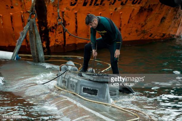 A Spanish Civil Guard diver stands over the refloated prow of a submarine used to transport drugs illegally in Aldan northwestern Spain on November...