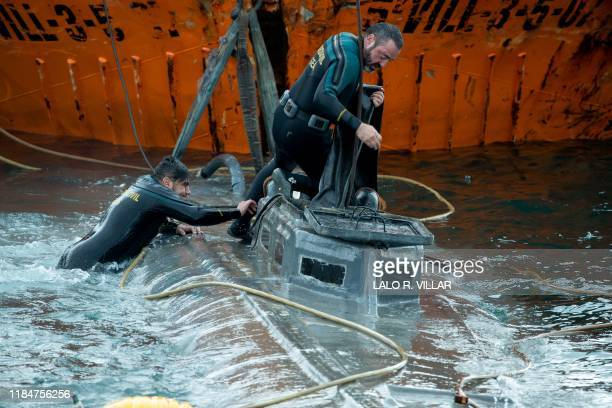 Spanish Civil Guard divers stand over the refloated prow of a submarine used to transport drugs illegally in Aldan northwestern Spain on November 26...