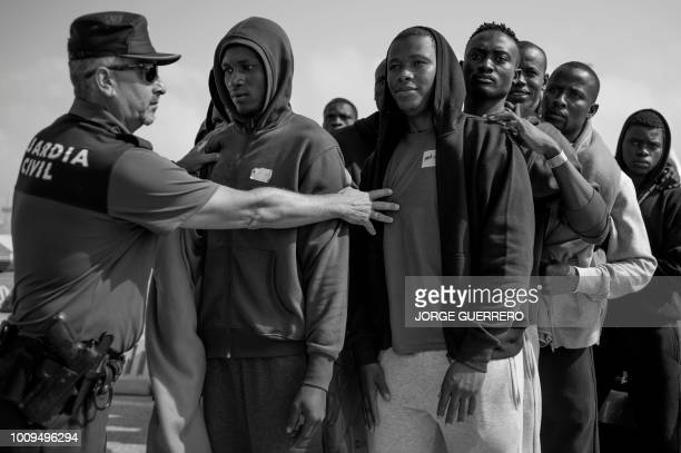 A Spanish Civil Guard gives instructions to African migrants rescued in the open sea to queue before being transferred at the harbour of Algeciras on...