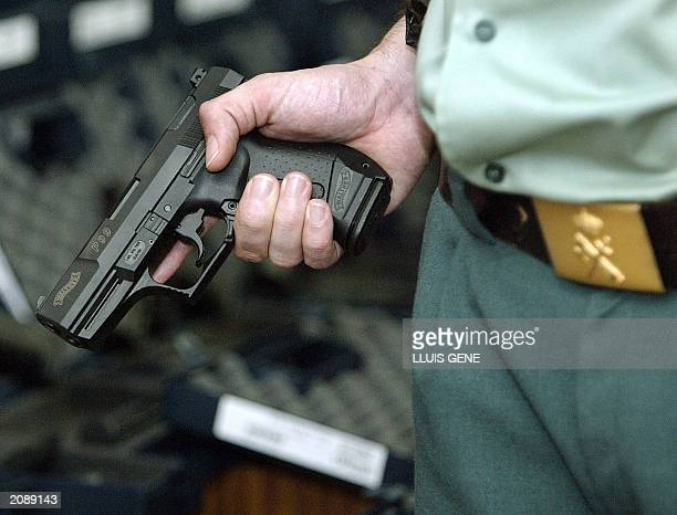 A Spanish civil guard shows 13 June 2003 one of 231 stolen automatic handguns recovered by Spanish police after the theft of 301 pistols from a...