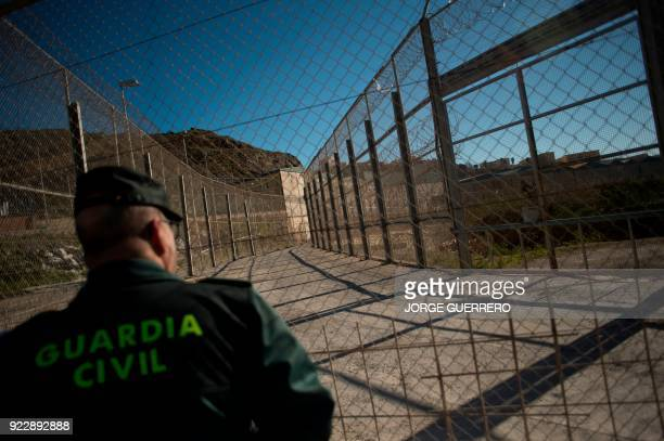 Spanish Civil Guard stands at the border fence between Morocco and the Spanish North African enclave of Ceuta on February 21, 2018.