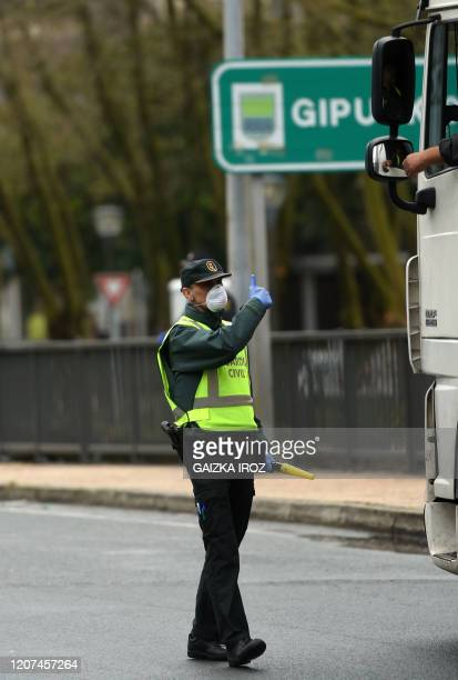 A Spanish civil guard talks to a truck driver as Spain refuse access to its territory to the vehicles in the context of measures taken to fight the...