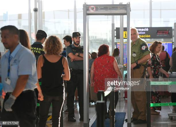 Spanish civil guards check passengers as they pass through a metal detector on August 14 2017 at Barcelona's El Prat airport Spain on August 14...