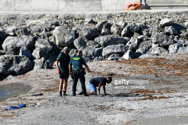 Spanish Civil guards help a migrant after he arrived swimming to the Spanish enclave of Ceuta from neighbouring Morocco on May 17, 2021. - More than...