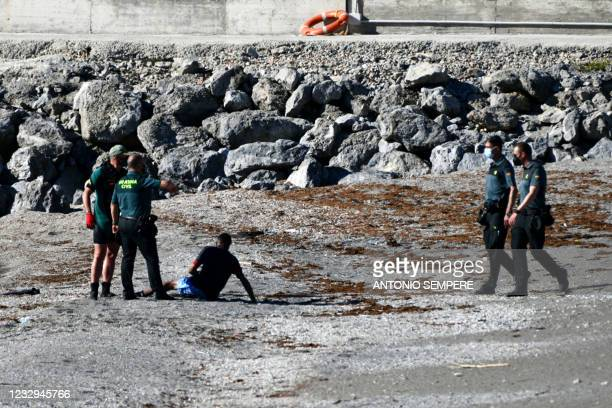 Spanish Civil guards speak with a migrant after he arrived swimming to the Spanish enclave of Ceuta from neighbouring Morocco on May 17, 2021. - More...