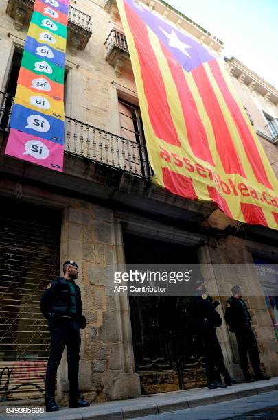 Spanish Civil Guards stand under a giant 'Estelada' in front of the headquarters of the company of waters of Girona on September 19 2017 The Spanish...