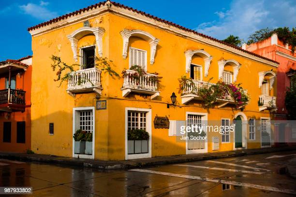 Spanish colonial house decorated with flowers is seen reflected on the pavement in the walled city on December 12 2017 in Cartagena Colombia After...