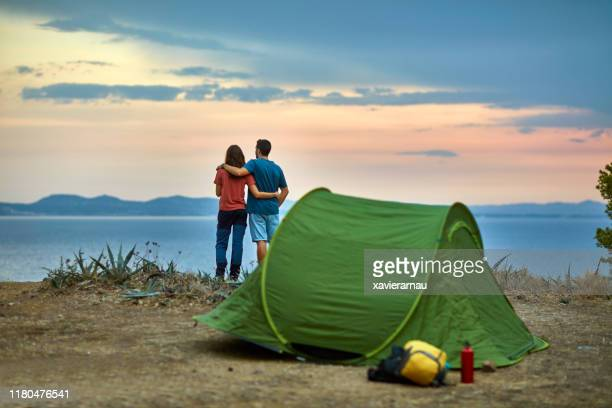 spanish couple enjoying mediterranean sunset at campsite - close to stock pictures, royalty-free photos & images