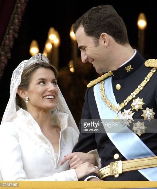 Spanish Crown Prince Felipe de Bourbon and his bride Letizia look at each other as the Royal couple appears on the balcony of Royal Palace May 22...