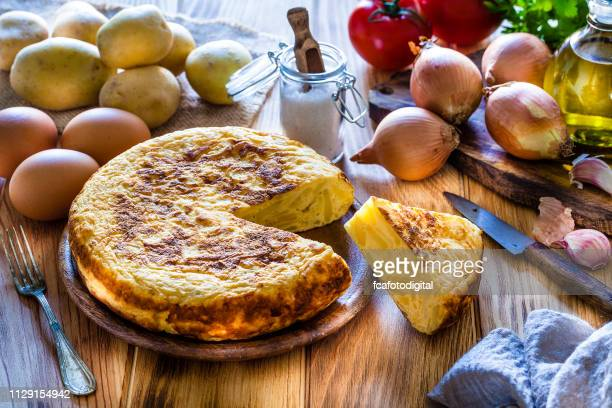 spanish cuisine: spanish tortilla with ingredients on wooden kitchen table - spanish culture stock pictures, royalty-free photos & images