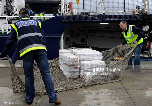 Spanish customs and policemen unload a shipment of cocaine from the vessel Riptide at the port of Vigo northwestern Spain on June 13 Spanish police...