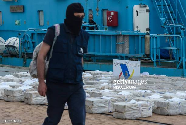 A Spanish customs officer walks past drug packages on June 3 2019 in the port of Vigo after seizing the vessel Gure Leire off the Spanish coast...