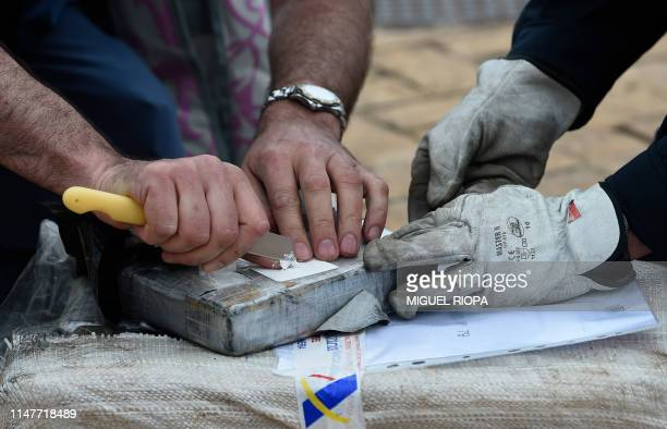 Spanish customs officers check a pack of cocaine in the port of Vigo after seizing the vessel Gure Leire carrying 2500 kg of cocaine on June 3 2019