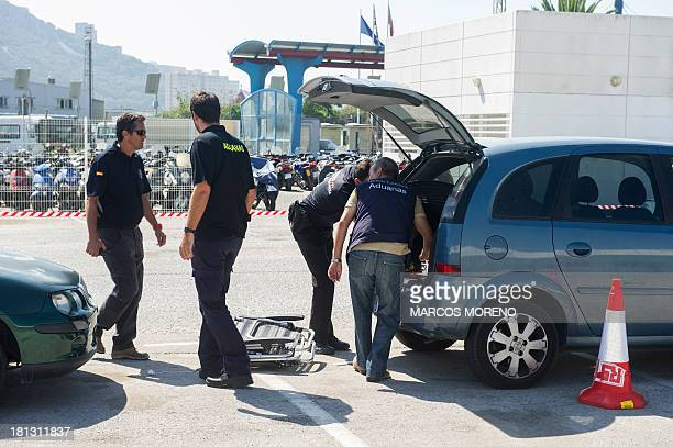 Spanish customs officials check a car after a customs' van equipped with a Mobile XRay Scanner scanned the car at the border between Spain and...