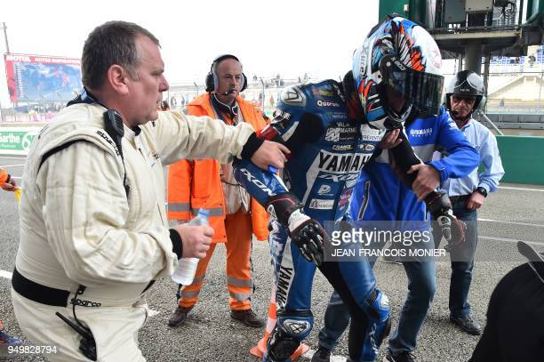 Spanish David Checa is escorted by his mechanics following his crash on his Yamaha GMT Formula EWC N°94 losing the first place after 470 laps in the...