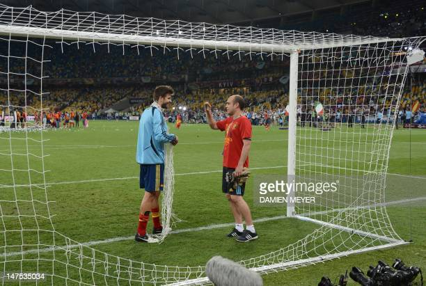 Spanish defender Gerard Pique cuts the goal net at the end of the Euro 2012 football championships final match Spain vs Italy on July 1 2012 at the...
