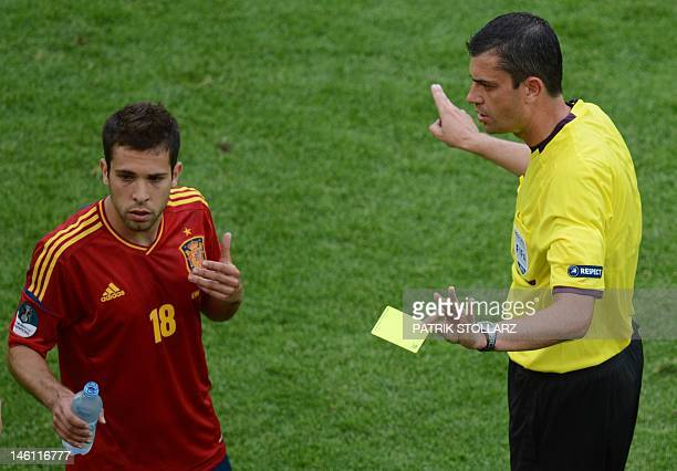 Spanish defender Jordi Alba is shown a yellow card by referee during the Euro 2012 championships football match Spain vs Italy on June 10 2012 at the...