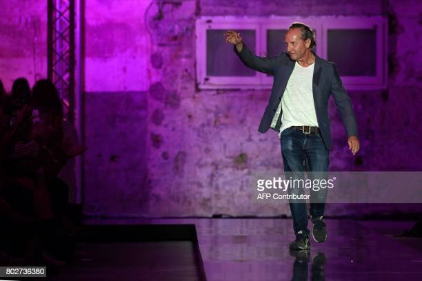 Spanish designer Custo waves from the catwalk after presenting his collection at the 080 Barcelona Fashion Week at Sant Pau hospital in Barcelona on...