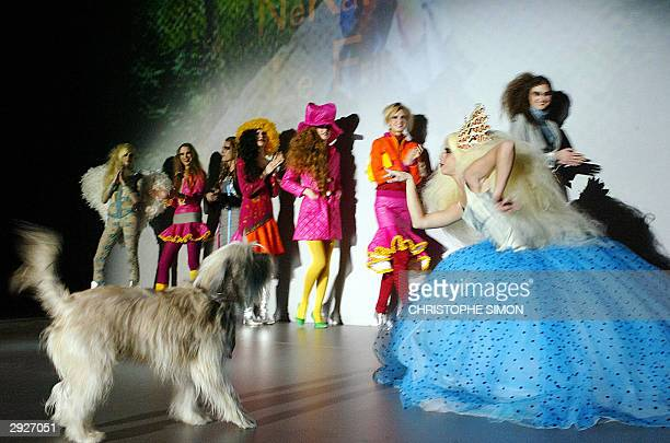 Spanish designer Nekane poses with her dog Friki as she displays an outfit she designed at the Pasarela Gaudi fashion show 04 February 2004 in...