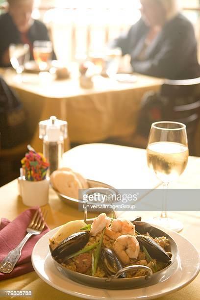 Spanish dish of paella and a glass of chardonnay wine, Patricks Side Street Cafe, Los Olivos, Santa Ynez Valley, California.