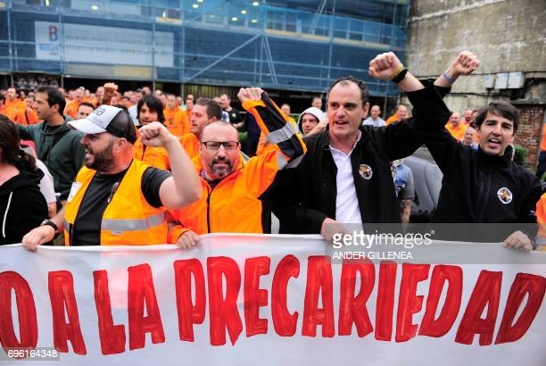 Spanish dockers gesture as they hold a banner reading No to precariousness during a twoday strike at the Port of Bilbao in the Spanish Basque city of...