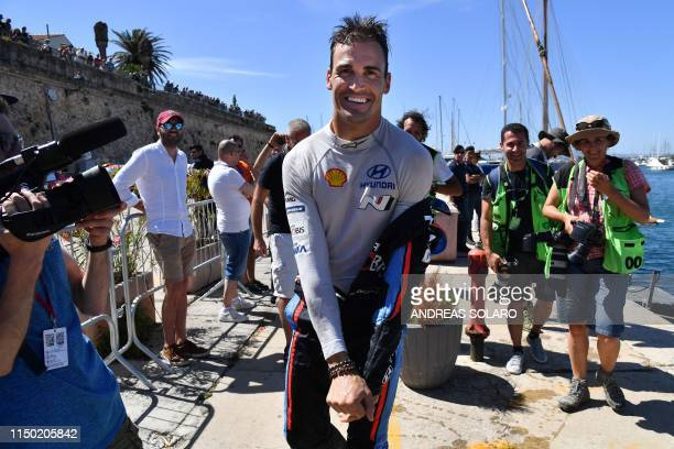 Spanish driver Dani Sordo takes off his driving suit after he jumped into the water at the port of Alghero, celebrating winning the 2019 FIA World...