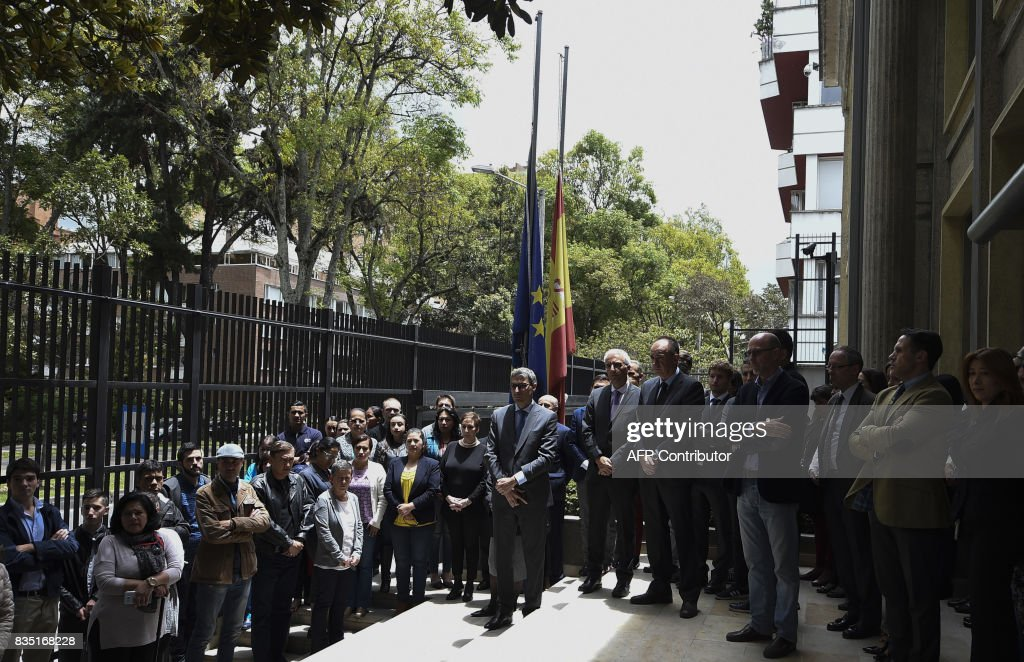 Spanish embassy staffers and Colombian people hold a minute's