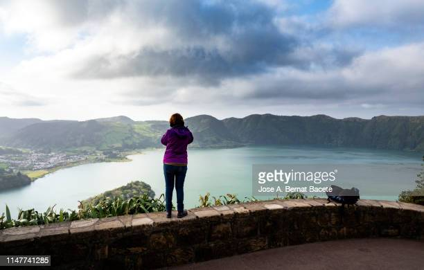spanish ethnicity woman taking a picture, view of a lake from a viewpoint. sao miguel island, azores islands, portugal. - lookout tower stock pictures, royalty-free photos & images
