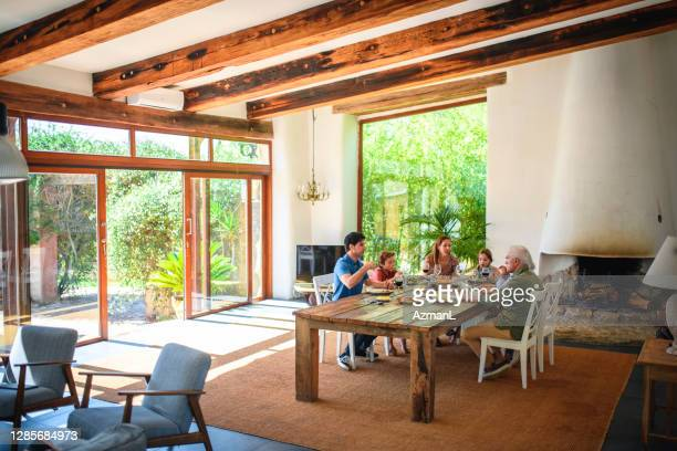 spanish family of six enjoying weekend meal at home - focus on background stock pictures, royalty-free photos & images