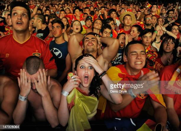 Spanish fans react while watching on a giant outdoor screen on Paseo de La Castellana street the UEFA EURO 2012 semi-final match between Spain and...