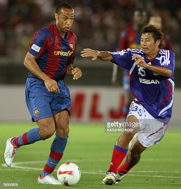 Spanish FC Barcelona forward Thierry Henry of France controls the ball as Japan's Yokohama F Marinos midfielder Ryuji Kawai tries to intercept during...