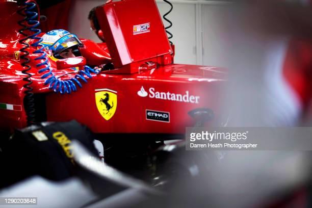 Spanish Ferrari Formula One racing driver Fernando Alonso sitting in his Ferrari F10 racing car in the Ferrari pit garage during practice for the...