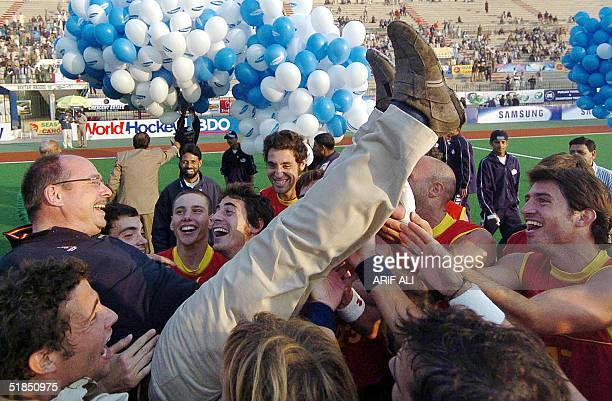 Spanish field hockey players lift team coach Maurits Hendriks as they celebrate victory at the end of men's Champions Trophy field hockey tournament...