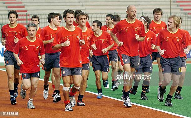 Spanish field hockey team players warm up for a practice session at the National Hockey Stadium in Lahore 02 December 2004 Spain's hockey team...