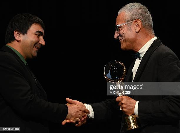 Spanish film director Luis Minarro and Georgian film director George Ovashvili shake hands as he receives the Grand Prix Crystal Globe Award for best...