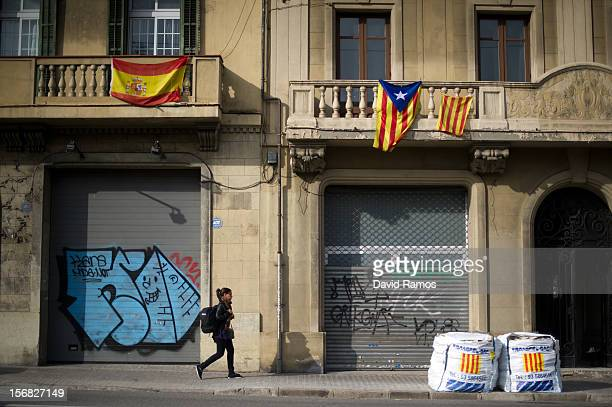 Spanish flag and a Proindependent Catalonia's flag are seen hanged as a woman walks beneath them on November 22 2012 in Barcelona Spain Over 5...