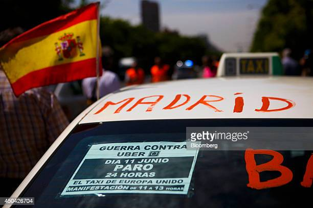 A Spanish flag flies from a taxi cab during a demonstration by cabbies to protest against the Uber Technologies Inc taxi app in central Madrid Spain...