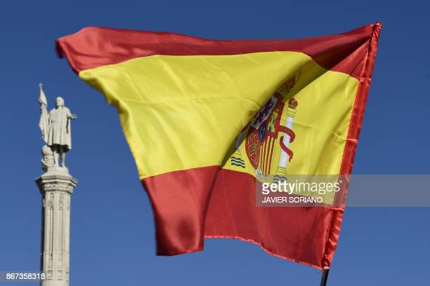 A Spanish flag flutters near the Christopher Columbus monument at Plaza de Colon in Madrid during a demonstration calling for unity on October 28 a...