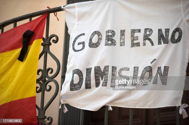 Spanish flag with a black ribbon hangs next to a banner that says government resignation during the first day of national mourning in Spain declared...