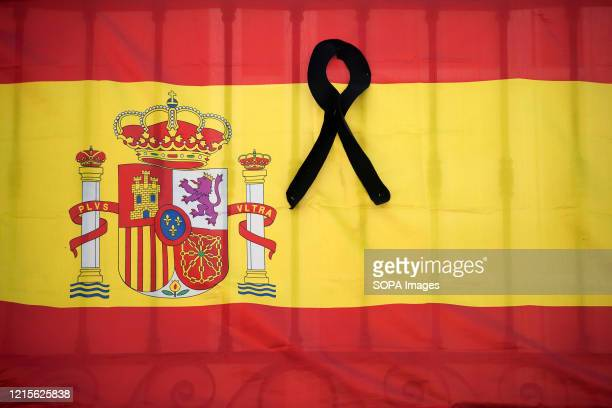 Spanish flag with a black ribbon hangs on a balcony during the first day of national mourning in Spain declared by the Spanish government as tribute...