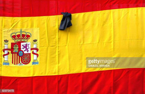 Spanish flag with a black ribbon is set on a wall in Madrid on the first anniversary of the train bombings 11 March 2005 Spain commemorates today the...